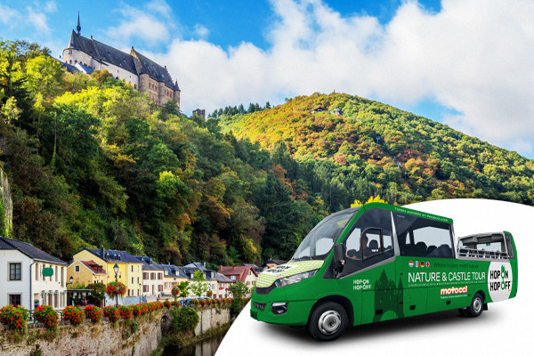 Convertible tourist bus with the city of Vianden in the background