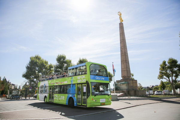 Hop On Hop Off Bus in front of the Gëlle Fra Monument at the Constitution Square