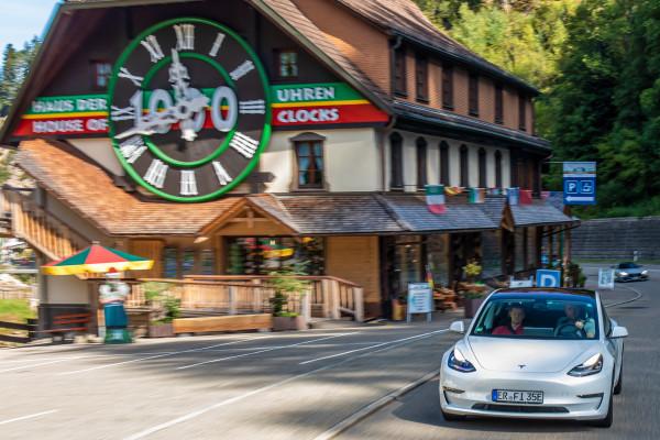 Tesla Model 3 vor Kuckucksuhr im Schwarzwald