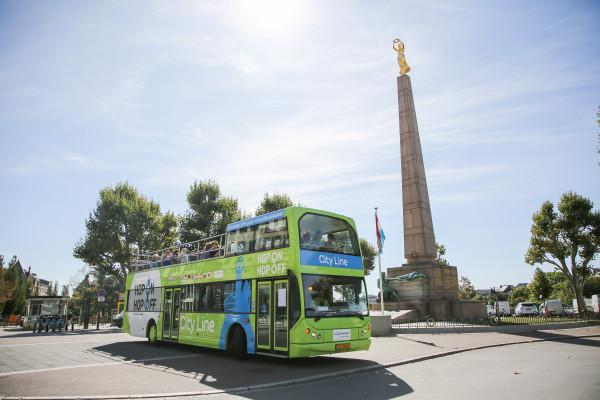 Bus Hop On Hop Off devant le monument du souvenir Gëlle Fra à la Place de la Constitution